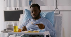 African young male patient eating food in hospital bed. Portrait of afro-american sick man sitting in bed and having meal on tray at hospital ward