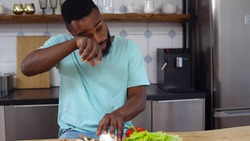 African young man crying chopping onion for vegetable salad in kitchen. Portrait of afro-american guy having tears cutting onion for vegetarian dinner at home
