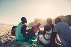 African young man singing and playing guitar on the beach. Group of four people having great time at the beach picnic.