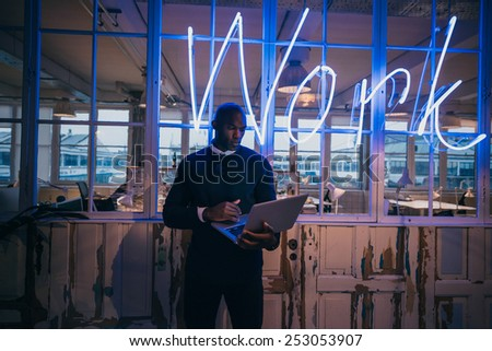 African young man standing in office using laptop computer. Business executive in office with big neon light work sign at the back on wall. #253053907