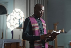African young priest reading the Bible during mass while standing near the altar in church