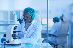 African young scientist sitting at his workplace and working with microscope during scientific experiment at office