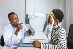 African young woman girl doing eye test checking examination using autorefractor in clinic or optical shop. Eyecare concept.