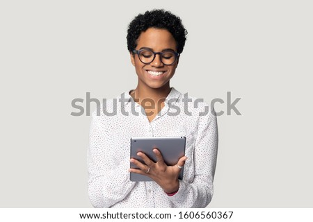 African young woman holding digital tablet isolated on gray background, student busy with assignment using educational websites useful applications, freelancer do remote distant work on-line concept