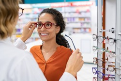 African young woman in optic store choosing new cool-down glasses with optician. Mixed race girl trying new eyeglasses with the help of the pharmacist. Multiethnic woman trying rest spectacle frame.