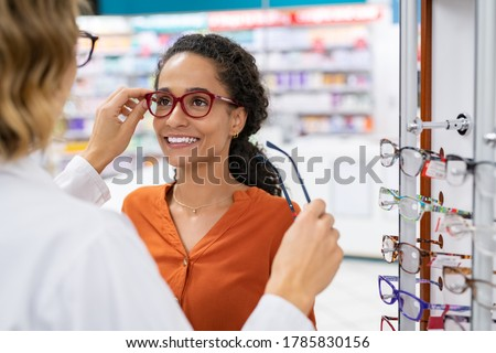 African young woman in optic store choosing new cool-down glasses with optician. Mixed race girl trying new eyeglasses with the help of the pharmacist. Multiethnic woman trying rest spectacle frame. Foto stock ©