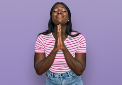 African young woman wearing casual striped t shirt begging and praying with hands together with hope expression on face very emotional and worried. begging.