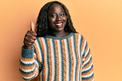 African young woman wearing wool winter sweater smiling happy and positive, thumb up doing excellent and approval sign