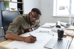 Afro-American architect working in office with blueprints.Engineer inspect architectural plan, sketching a construction project. Portrait of black handsome man sitting at workplace. Business concept.