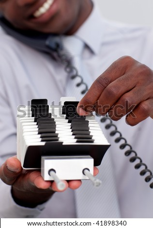 Afro-American businessman on phone and looking at an index holder
