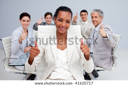 Afro-American businesswoman and her team with thumbs up in the office