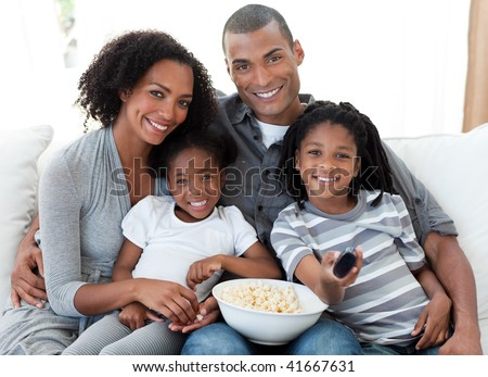 Afro-American family watching television and eating popcorn at home