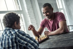 Afro American father and son in casual clothes are playing chess while spending time together at home, man is smiling