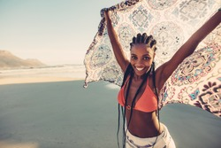 Afro american female standing on the seaside with her scarf. Beautiful woman standing on the beach with fabric.