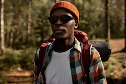Afro american guy in stylish hat and glasses walking in forest. Lonely traveler go for hiking and camping. Weekend trip, escape from city, calm rest in nature. Travelling concept