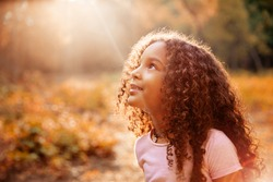 Afro american happiness little girl with curly hair receives miracle sun rays from the sky