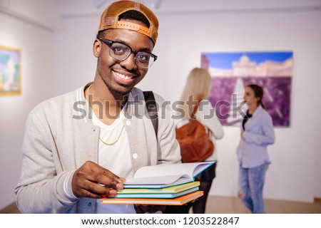 Afro-american hipster student man in eyeglasses holding colorful stack of books, smile, looking at camera. Guy in art gallery with two girls on background. Multi ethnic, study abroad, culture concept. stock photo