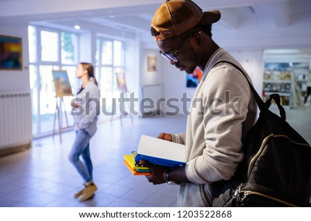 Afro-american hipster student man in eyeglasses with backpack holding colorful stack of books, reading one of book. Guy in art gallery. Multi ethnic, study abroad, culture concept. stock photo