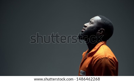 Afro-american imprisoned male praying looking up at light, talking to god, faith Stock photo ©