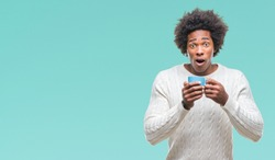 Afro american man drinking cup of coffee over isolated background scared in shock with a surprise face, afraid and excited with fear expression