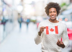 Afro american man flag of Canada over isolated background with a happy face standing and smiling with a confident smile showing teeth