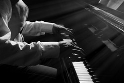 Afro American man hands playing piano in darkness