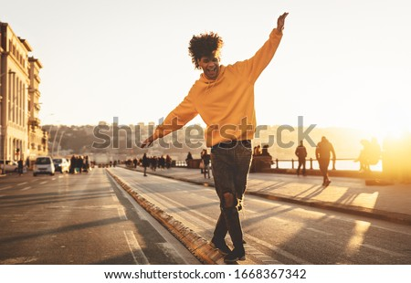 Afro American man having fun walking in city center - Happy young guy enjoying time a sunset outdoor - Millennial generation lifestyle and positive people attitude concept