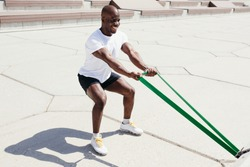 Afro American man in white t-shirt and black shorts doing exercise on his hands squatting with elastic fitness tape outside