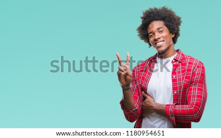 Afro american man over isolated background smiling with happy face winking at the camera doing victory sign. Number two.