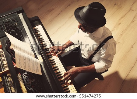 Afro American man playing piano - Shutterstock ID 551474275