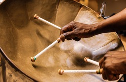 Afro american man plays the steel drum using two hands and four drumsticks