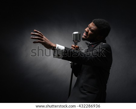 afro american man singing into...