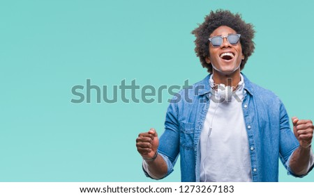 Afro american man wearing headphones listening to music over isolated background celebrating mad and crazy for success with arms raised and closed eyes screaming excited. Winner concept #1273267183