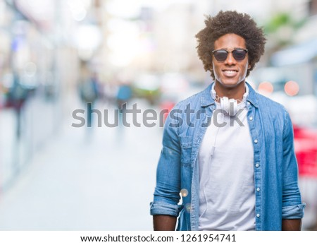 Afro american man wearing headphones listening to music over isolated background with a happy and cool smile on face. Lucky person. #1261954741