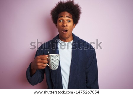 Afro american man wearing pajama drinking coffee standing over isolated pink background scared in shock with a surprise face, afraid and excited with fear expression