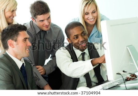 Afro-American manager explaining a job to his team from a computer