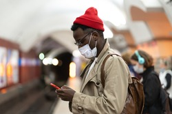 Afro-American millennial man in trench coat, red hat wearing face mask as protection against  covid-19, flu virus, waiting for the train at subway station, using mobile phone. New normal, pandemic.