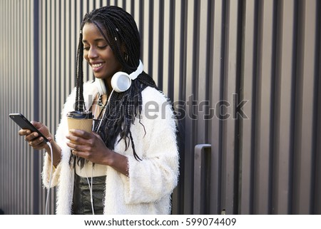 Afro american teen hipster girl with white headphones using smartphone and 5G wireless connection to blogging and posting in social networks receiving feedback from followers admire multimedia files