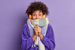 Afro American woman feels very cold during freezing weather wears purple jacket and warm scarf around neck wals on street during winter listens music via wireless headphones keeps hands together