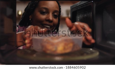 Afro-american woman using the microwave oven to heating food. View from inside microwave of african female heating up plastic container with buckwheat and chicken