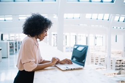 Afro american woman working on digital netbook connected to wireless internet in office company, prosperous young female entrepreneur typing online publication on laptop in financial industry