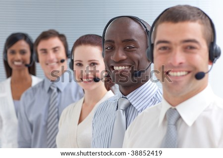 Afro-American young businessman smiling and standing  in a call center in a line