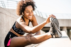 Afro athlete woman stretching legs before exercise.