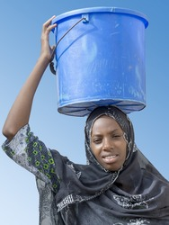 Afro beauty carrying a bucket of water on her head