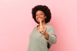afro black woman smiling proudly and confidently making number one pose triumphantly, feeling like a leader