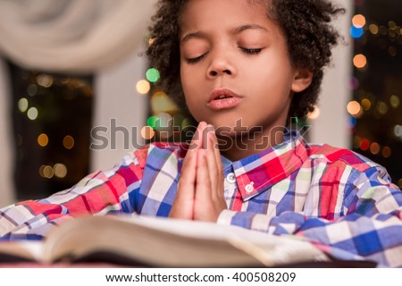 Afro child praying. Black kid prays beside window. Boy\'s evening prayer. Gesture of faith.