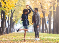 Afro couple in love dancing together in autumn park, free space