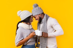 Afro couple in winter clothes bonding while having tea or coffee, yellow background