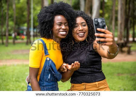 Afro descent girls using smartphone in the park