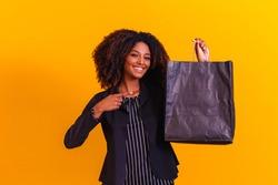 Afro executive woman with black shopping bag. Blackfriday concept